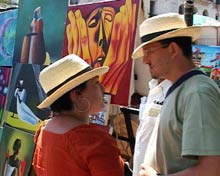Tourists surrounded by colorful canvases.