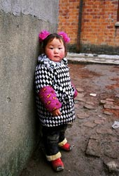 Young girl leans against a wall