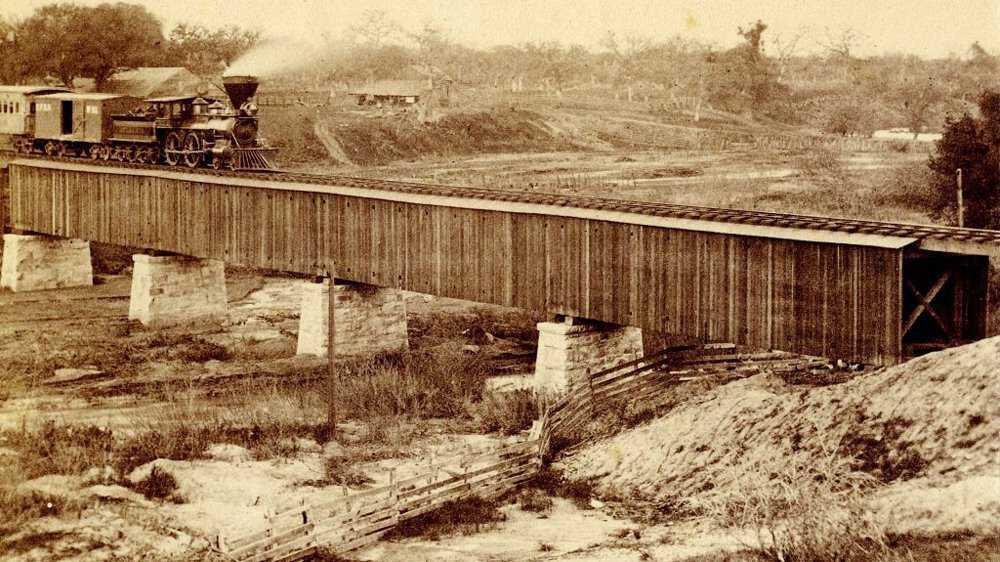 Iron-further-reading-Central-Pacific-Railroad-train-crossing-a-bridge-circa-1866-PD.jpg