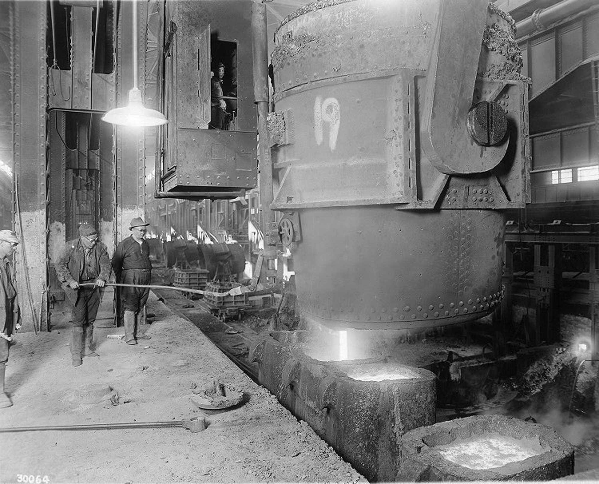 Steel-workers-gaze-on-as-molten-steel-is-poured-from-ladle-to-casts-at-Homestead-Steel-Works,-December-31,-1914.-PD..jpg