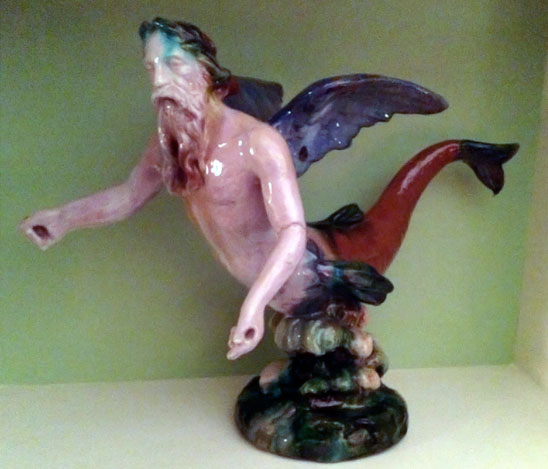 art pottery statue of neptune -- bearded man with wings, a fish tail, and a broken left arm