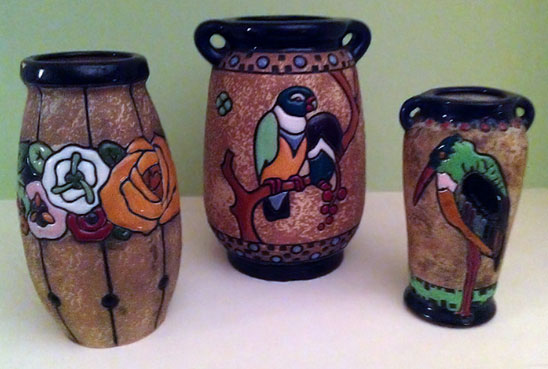 three art pottery vases, left with colorful flowers, center with a parrot, right with a toucan-like bird