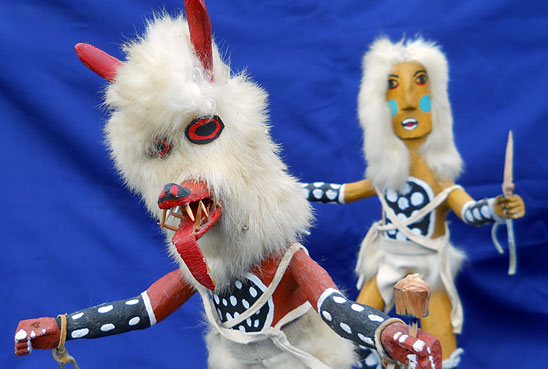 two southwest native american dolls. one red and wolf-like, the other yellow and more human looking