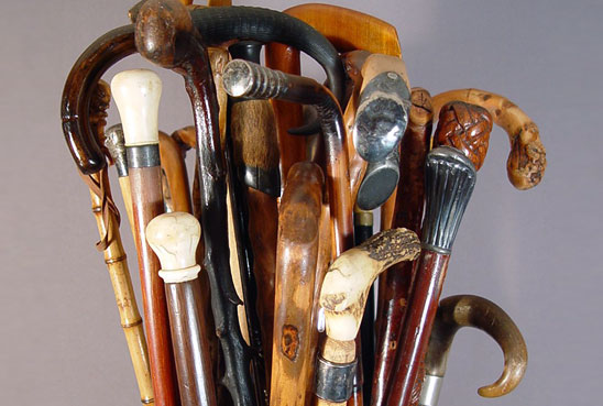 photograph of approximately two dozen walking sticks and canes