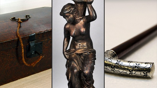 photograph of three early 20th century objects. From left to right: wooden box, brass lamp fixture in the shape of a nude woman, and a silver-headed cane