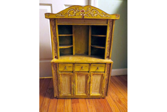 Child-size mustard-colored cupboard decorated with stencils