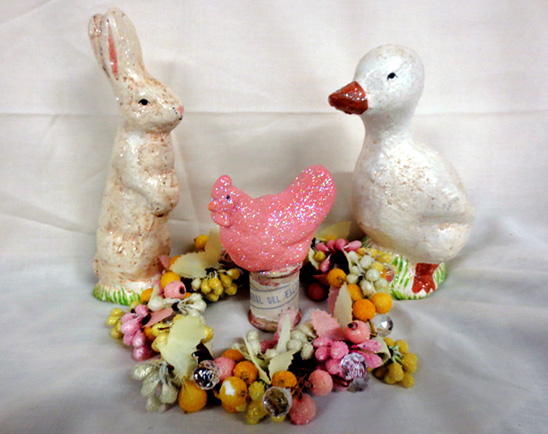 Vintage easter objects: a white rabbit, a pink sparkly chicken on a spool of thread, and a white duck