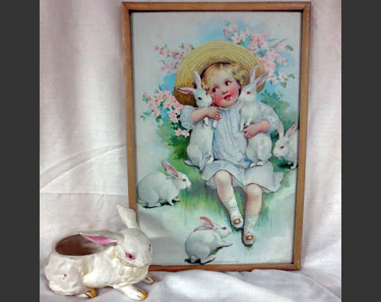 A vintage ceramic planter in the shape of a rabbit next to a 1906 chromo-lithograph of a girl dressed in whites, playing with bunnies