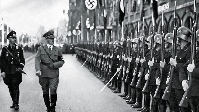 Adolf Hitler and Heinrich Himmler review a parade of Hitler s personal guard
