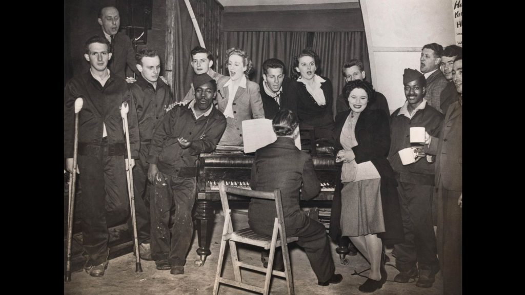 GIs and ENSA performers gathered around a piano, 1944