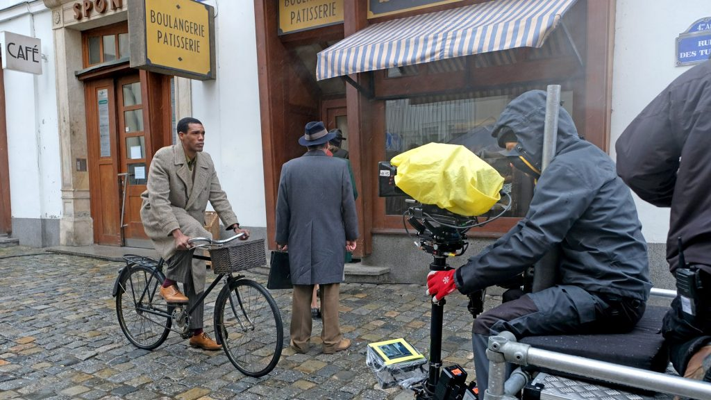 Parker Sawyers riding a bike for a scene in World on Fire, Season 1