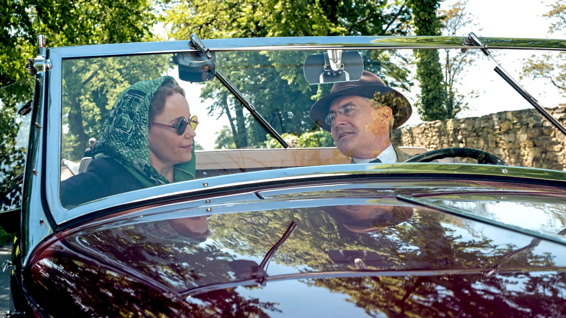 Actress Sofia Helin as Crown Princess Martha in a car with actor Kyle Mclaughlin as Franklin Roosevelt in Atlantic Crossing.