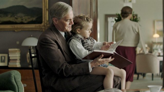 Actor Kyle MacLachlan as President Franklin Roosevelt with a child in his lap in Atlantic Crossing.