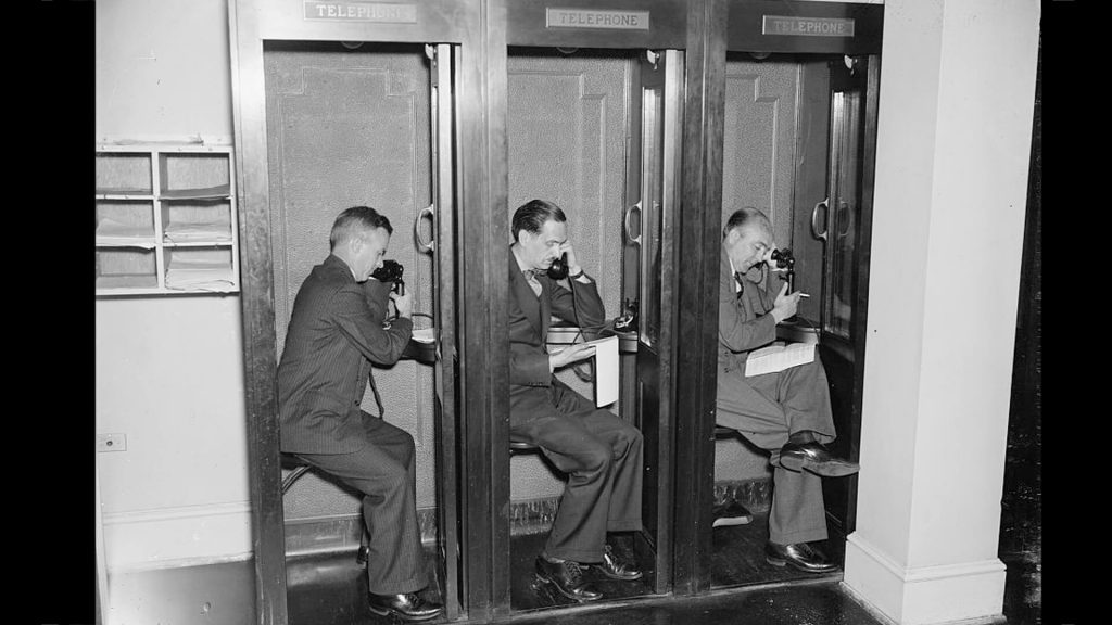 Reporters in phone booths at the White House press room, 1937.