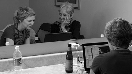 Mary Wharton showing footage to Joan Baez in her dressing room after a shoot.