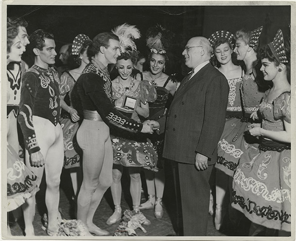 Antony Tudor receives a testimonial watch from impresario S. Hurok after an all Tudor program at the Metropolitan Opera with Nora Kaye looking on. 1945.