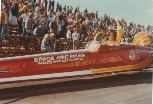 Smiling woman sits in a racecar and waves to the camera. In the bleachers behind her, spectators watch.