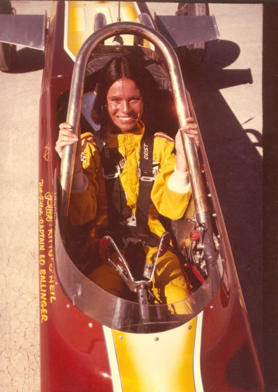 Smiling woman in a yellow racing suit sitting in a racecar