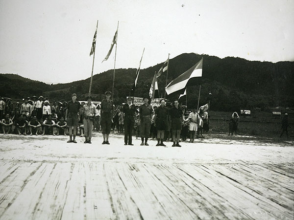 British Major Tom Harrisson and some of his Australian commandoes on the bamboo airstrip in June, 1945. Harrison and his men launched an audacious rescue plan to get the US airmen out of Borneo. On the right of the flagpoles is the head of a senior Japanese official, brought to Harrisson as a gift from one of the local headmen.