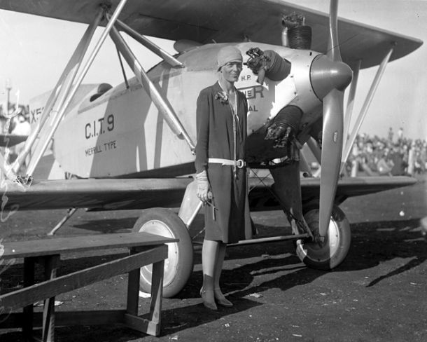 Amelia Earhart — wearing a dress, standing beside a plane, circa 1928. Publication:Los Angeles Daily News Publication date:1928 Source:Los Angeles Times photographic archive, UCLA Library