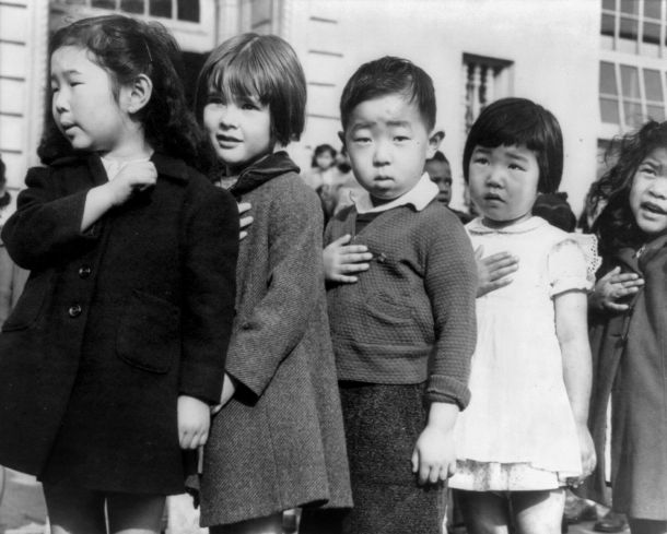 First-graders, some of Japanese ancestry, at the Weill public school, San Francisco, Calif., pledging allegiance to the United States flag. April 1942. Photo attributed to Dorothea Lange