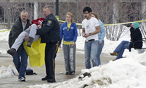 A Northern Illinois University police officer, center, helps a victim after a shooting on the campus in DeKalb, Ill.