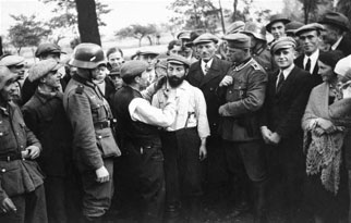 The local community: A group of German soldiers and civilians looks on as a Jewish man is forced to cut the beard of another in Tomaszow Mazowiecki, Poland, September–October 1939.