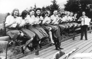 The perpetrators' community: SS female auxiliaries and Karl Höcker, the adjutant to Auschwitz's camp commander, eat bowls of blueberries to accordion music, Solahütte retreat near Auschwitz, Poland, 1944.