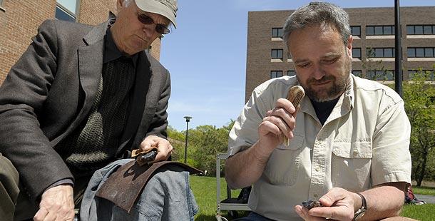 Alan Alda and John Shea work on stone tools side by side. Photo: © Larry Engel 2008
