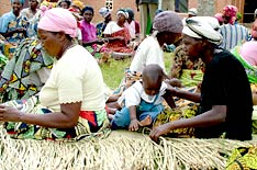 A group of women are seated weaving baskets from reeds.