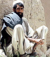 Photo of an Afghan man resting against a wall