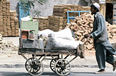 Photo of an Afghan man pushing a heavy cart