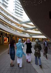 Photo of young Turkish women walking in a commercial center.